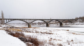 Bridge over the frozen Volga River in Staritsa, overcast winter Stock Photography