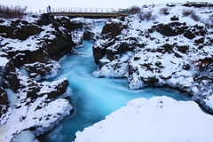 Bridge over Glacial River. Deep blue glacial river running through a waterfall in Barnafoss, Iceland Stock Images