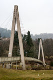 Bridge over golf course triangular. Triangular shaped bridge with grey sky and green forest surrounding it Royalty Free Stock Image