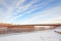 Bridge Over an Icy River. Landscape of a bridge over an icy river with snow covered banks Stock Photography