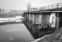 Bridge over an irrigation canal. Black and white photo Royalty Free Stock Image