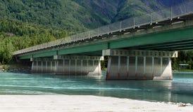 Bridge Over the Kenai 2. Glacier blue water flows under a concrete and steel bridge Stock Image