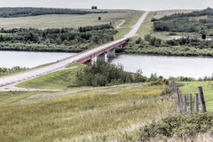 Bridge over a lake. Long bridge expanding over a lake with rolling hills Stock Photo