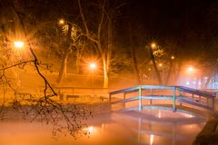 Bridge over a lake in Miskolctapolca, Hungary. Beautiful night scene with a wooden bridge over the lake illuminated by lights in  Miskolctapolca town, Hungary Stock Photography
