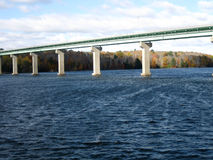 Bridge over large body of water. Bridge with autumn foliage in the background Royalty Free Stock Photo