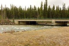A bridge over the liard river in canada. A swollen, springtime river rushing under a bridge in british columbia stock photo