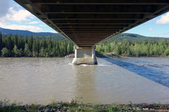 A bridge over the liard river in canada. Underneath a large bridge spanning a swollen river in the springtime Stock Images