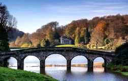 Bridge over main lake in Stourhead Gardens during Autumn. Royalty Free Stock Images