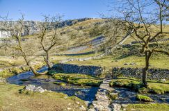 Bridge over Malham Beck. Low bridge over Malham Beck near Malham Cove  in attractive landscape with footpath and gate in the stone wall Royalty Free Stock Image