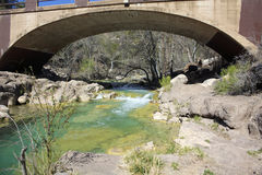 Bridge over mountain creek. A bridge over colorful spring fed creek in Arizona stock photography