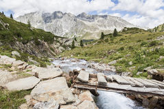 Bridge over mountain creek in Alps. Royalty Free Stock Photography