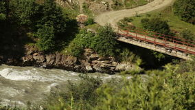 Bridge over mountain river. Mountain river and the bridge across it in the mountainous part of Georgia's Upper Svaneti stock footage