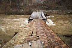 Bridge over a mountain river. A small bridge across a rushing mountain river in the high water period stock photo