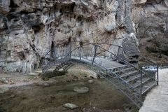 Bridge over the mountain river. Small metal bridge with handrails over a mountain river in the gorge royalty free stock images