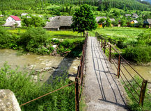 Bridge over mountain river. The village in the mountains on the banks of the river Royalty Free Stock Photography