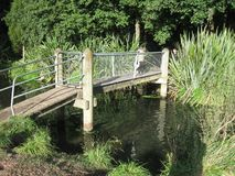 Bridge over muddy water. A small footbridge with gate and handrails royalty free stock photography