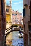 Bridge over a narrow canal sidelined by old buildings in Venice Royalty Free Stock Images