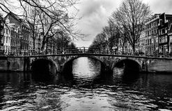 A bridge over one of the canals in Amsterdam centrum. Black and white photo of this tree tunnel bridge that goes over one of the canals in Amsterdam centrum on a Royalty Free Stock Photography