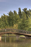 Bridge Over Pond. Bridge crossing a pond with blue sky and trees in background Stock Images