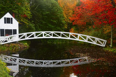 Bridge over a pond and a house on the bank reflected in the water in the autumn park. Arch bridge across the pond and a small house on the beach, reflected in Stock Photography