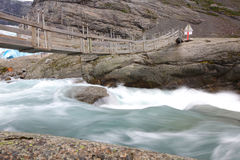 Bridge over rapid runoff water from glacier Royalty Free Stock Image