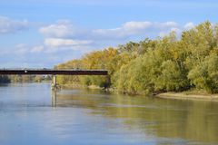 Bridge over the river. Autumn leaves on poplars along the river bank. royalty free stock photos