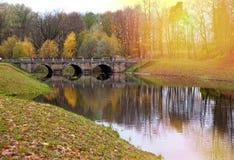Bridge over a river in autumn park Stock Photos