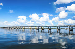 Bridge over the river on a background of the blue cloudy sky Stock Images