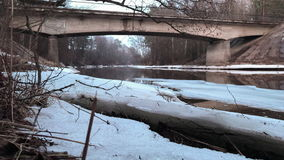 Bridge over the river in early spring when the snow has not yet melted away. Time lapse video. stock footage