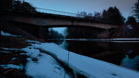 Bridge over the river in early spring when the snow has not yet melted away. Time lapse video. stock video