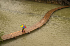 Daily on the bridge over the river. Fenghuang, China – June 9 : Daily life of villager on wooden bridge in the old town on June 9, 2015 in Fenghuang city Stock Photo