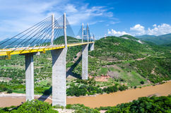 Bridge over river with green mountains in sunny colorful day. Modern road bridge over river in a colorful landscape with green mountains, blue sky, white clouds Stock Image