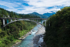 Bridge over river in Japanese Alps Royalty Free Stock Photo