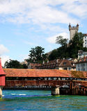 Bridge over the river in Luzern. A wooden bridge over the river in Luzern with a castle in the background Stock Image