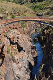 Bridge over river. A narrow bridge over a cliff with a blue river below Stock Images