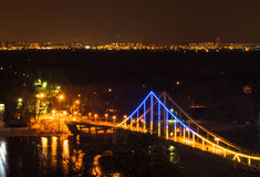 The bridge over the river at night. On the background of the city Royalty Free Stock Photo