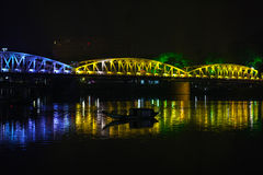 Bridge over the river at night with colorful lights, reflecting Royalty Free Stock Image