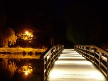 The bridge over the river at night. Wooden bridge over the river at night, beautifully lit Royalty Free Stock Photos