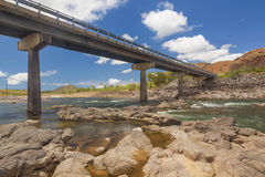 Bridge over the river. Picture of a bridge over a river at midday.  The sky is blue and cloudy.  There are some rocks at the forefront Stock Photos