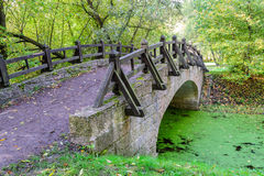 The bridge over the river. Small, beautiful bridge across the tranquil river. Bridge with handrails in autumn Park or woods. On the bridge are autumn leaves royalty free stock image