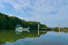 The bridge over the river with a small fishing boat. The bridge over the river with a small white fishing boat anchored off the fish royalty free stock photos