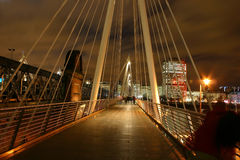 Bridge over river Thames by night. With people passing by on it stock photos