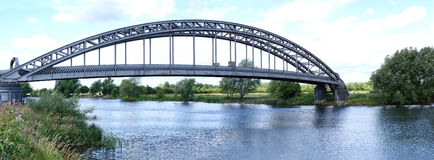 Bridge Over River Trent. Panoramic image of a metal bridge spanning the River Trent before the mouth of the River Derwent, Nottinghamshire, England Stock Images