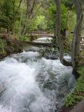 Bridge over roaring creek stock photography