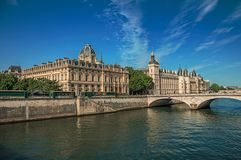 Bridge over the Seine River and the Conciergerie building with sunny blue sky at Paris. Royalty Free Stock Images