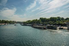 Bridge over Seine River and touristic boats under sunny blue sky in Paris. Paris, northern France - July 07, 2017. Bridge over Seine River and touristic boats Royalty Free Stock Photos
