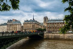 Bridge over Seine river and typical building in Paris, France. PARIS, FRANCE - MAY 24, 2016: People o the bridge over Seine river and typical parisian buildings Stock Photo