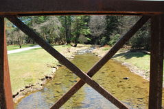 Bridge over shallow waters. View of crystal clear creek through old iron bridge royalty free stock photos