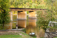 Bridge over the Shenandoah River. Stunning shot of a man standing on a stone wall overlooking a river next to a bridge Stock Photo