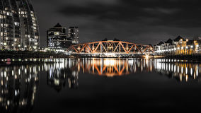Bridge over a small river with long reflections. Industrial steel bridge over a still river at night. Long reflections a the bridge and nearby houses are seen on Royalty Free Stock Photos